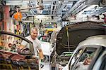 Montage des portes en voiture dans une usine automobile de travailleur