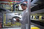 Inspecter les voitures dans l'usine automobile de travailleur