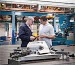 Ingénieurs discutant pièces usine automobile