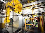 Rouleaux de travailleur avec de l'acier dans l'usine de voiture