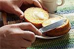 A Man Buttering a Halved Corn Muffin