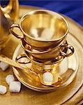 Or tasses à thé, soucoupes et cuillère ; Avec les Cubes de sucre