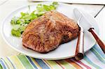 Rôti de porc assaisonné sur un plateau blanc ; Couteau et fourchette