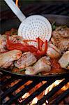 Paella in einer großen Pfanne auf offenem Feuer