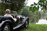 Senior homme regardant le lac de voiture antique