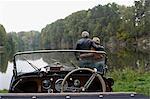 Couple senior en regardant le lac, en face de voiture antique