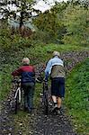 Altes Paar Fahrrad bergauf schieben