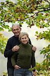 Debout de couple senior sous les feuilles