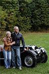 Couple senior, appuyé contre une voiture antique