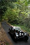senior homme volant vers le bas de la route de campagne en voiture antique