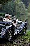 Senior homme assis dans une voiture antique près du lac