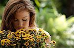 Junge Frau im Hauptfeld der Gänseblümchen riechen