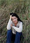 Woman sitting in wild grass, hand in hair