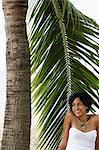 Jeune femme assis sous l'arbre de paume et souriant