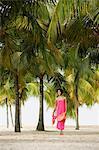Jeune femme marchant sur la plage, sous les cocotiers.