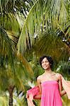 Junge Frau unter grünen Kokospalmen und lächelnd.