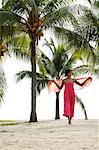 femme qui marche sur la plage sous les cocotiers port rose.