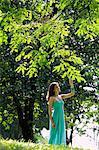 Junge Frau, die Blätter eines Baumes zu berühren.