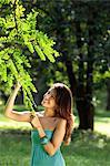 jeune femme regardant les feuilles de l'arbre et souriant
