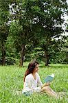 Frau sitzt auf dem Gras, ein Buch zu lesen