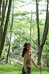 Junge Frau zu Fuß unter Bäumen