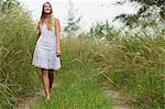 Blonde woman walking on grassy path