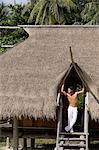 Young man standing in doorway of island house