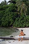 Man sitting on felled palm tree