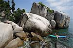 man kayaking near rocks