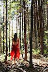 Femme en robe rouge se promenant dans la forêt