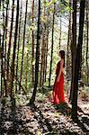 Femme en robe rouge debout dans la forêt