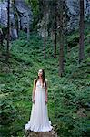 Jeune femme debout dans la forêt