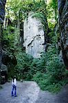 jeune femme entourée de murs de gros rocher