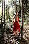 jeune femme en robe rouge, marche en forêt