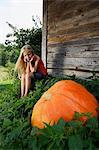 girl sitting by a growing pumpkin