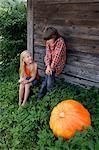 boy and girl next to pumpkin