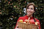 Jeune femme avec panier rempli de pommes