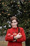 jeune femme tenant les bras plein de pommes