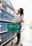 Femme atteignant pour produit en supermarché