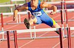 Male hurdler jumping over hurdle