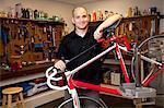 Man with bicycle in repair shop