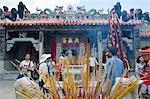 Worshipper offering incense at Pak Tai Temple during the Bun festival, Cheung Chau, Hong Kong