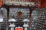 Heavy wishing stone at Fushimi Inari Taisha Shrine, Kyoto, Japan