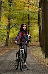 Junge Frau nehmen Rest aus dem Fahrrad durch den Wald