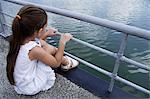 young girl sitting over lake