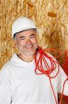 Porträt von lächelnd männlich Bauarbeiter mit einem roten elektrischen Draht