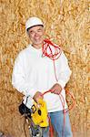 Porträt von glücklichen männlichen Bauarbeiter holding eine Motorsäge und eine rote elektrische Kabel