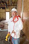 Porträt von lächelnd männlich Bauarbeiter holding eine Motorsäge und eine rote elektrische Kabel