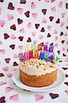 Nahaufnahme der Geburtstagstorte mit Kerzen in Herzform-Hintergrund