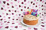 Nahaufnahme der Geburtstagskerzen auf Kuchen in Herzform-Hintergrund